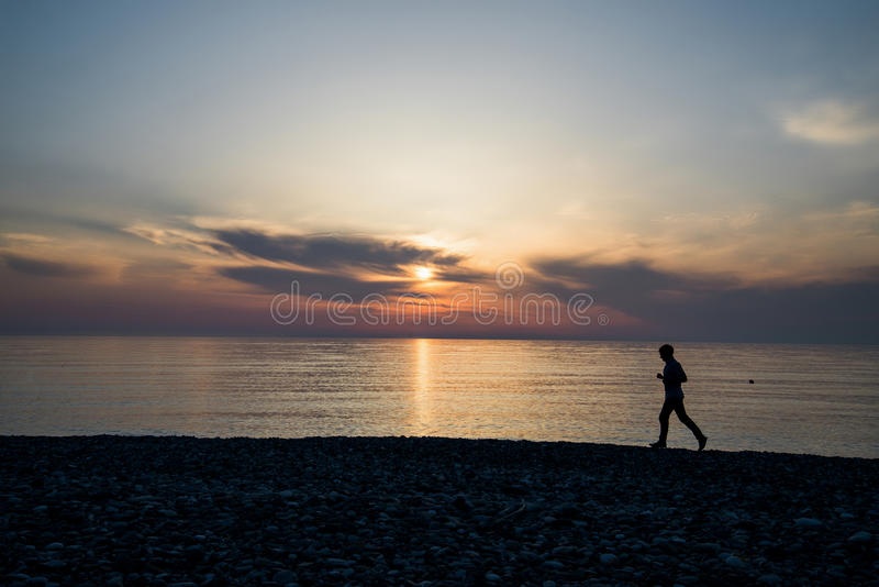 Silhouette of man running on the beach at sunset.  royalty free stock photo
