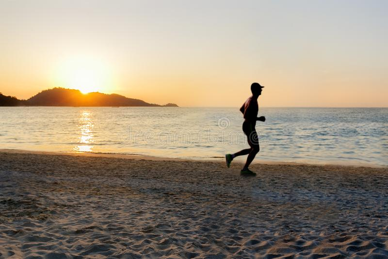 Silhouette of man running on the beach at sunset. Sport and healthy lifestyle royalty free stock photography