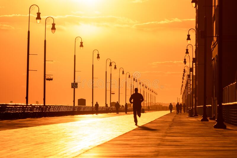 Silhouette of a man running on a boardwalk at sunset. Long Beach NY. Silhouette of a man running on a boardwalk at sunset. Outdoor activity under golden light royalty free stock photography