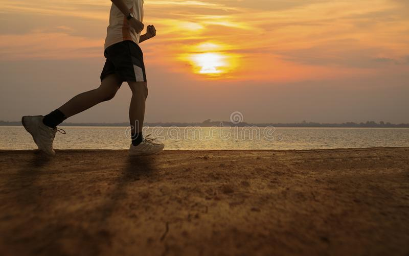 Silhouette of man running with sunrise or sunset background stock image