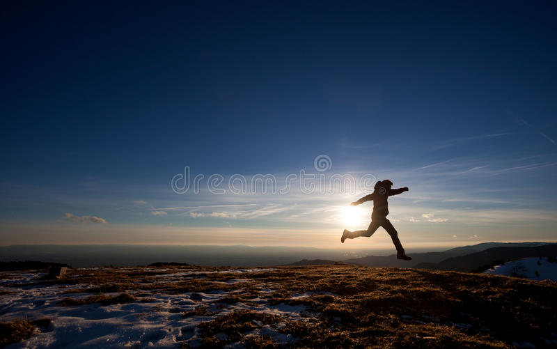 Silhouette of man running in sunset sky. On hill stock photos