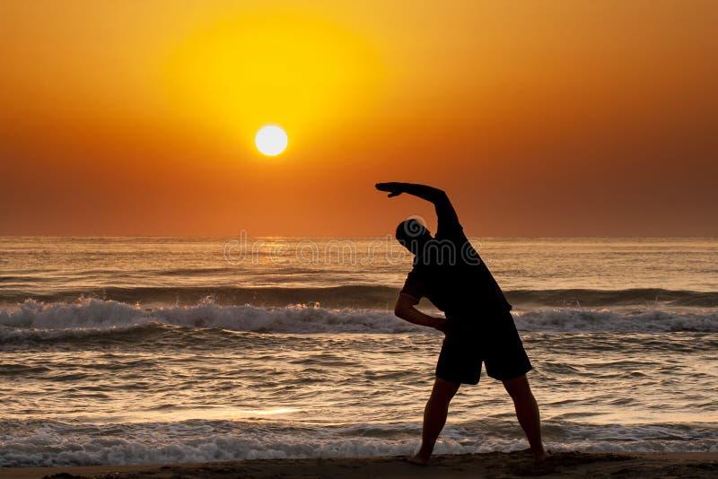 Silhouette Man Sea Sunrise Doing Fitness Exercise royalty free stock photo