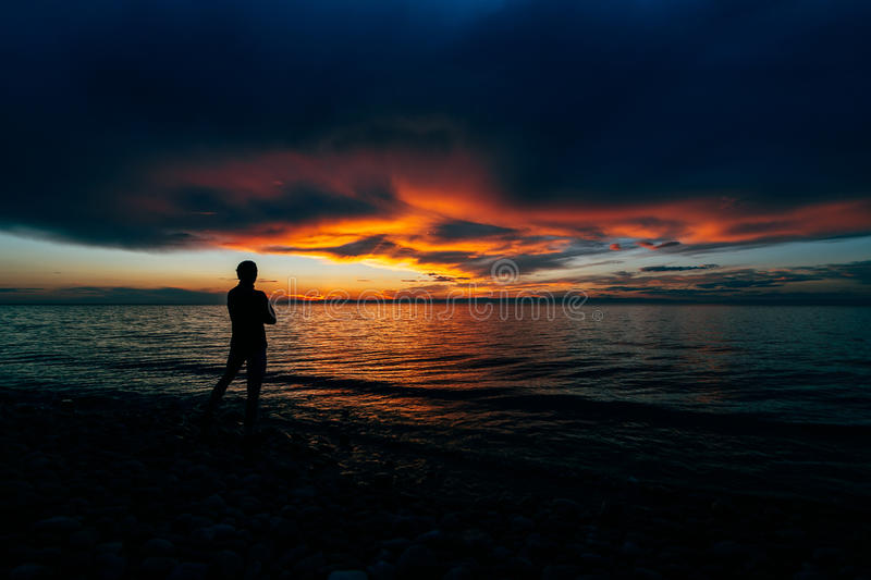Silhouette of man on the shore of a lake sunset background stock image