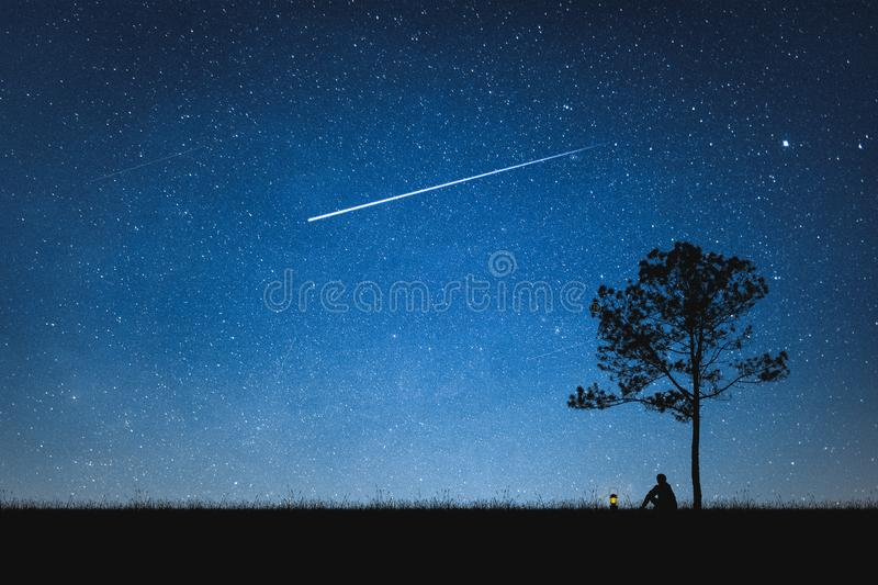Silhouette of man sitting on mountain and night sky with shooting star. Alone concept. Star stock photos