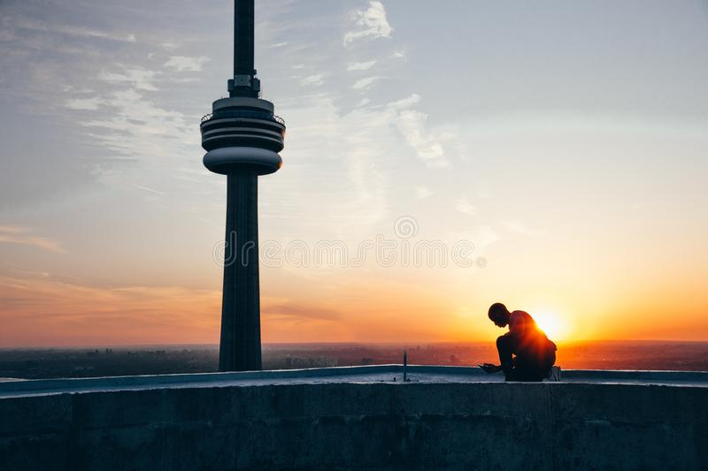 Silhouette of a Man Sitting Near Black Tower Near Body of Water during Sunset stock photo