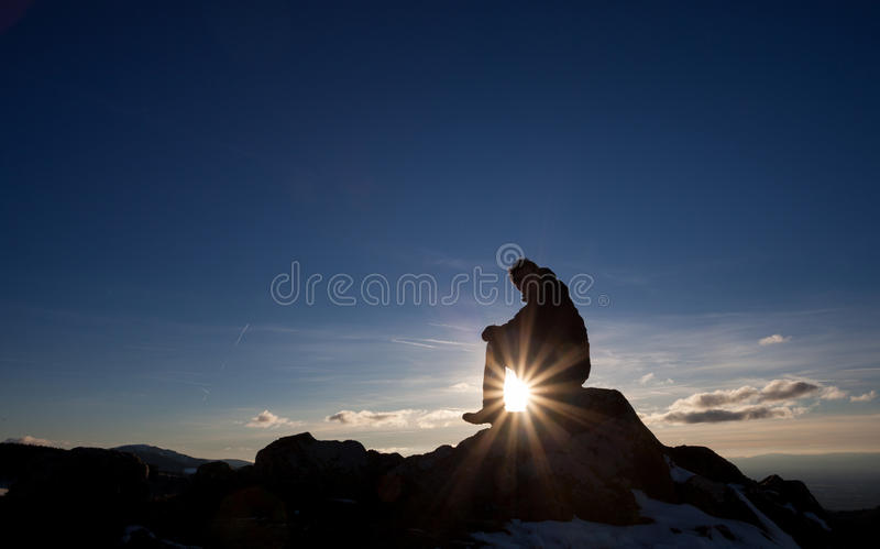 Silhouette of man sitting on peak in sunset. Silhouette of man sitting on mountain peak in sunset royalty free stock image