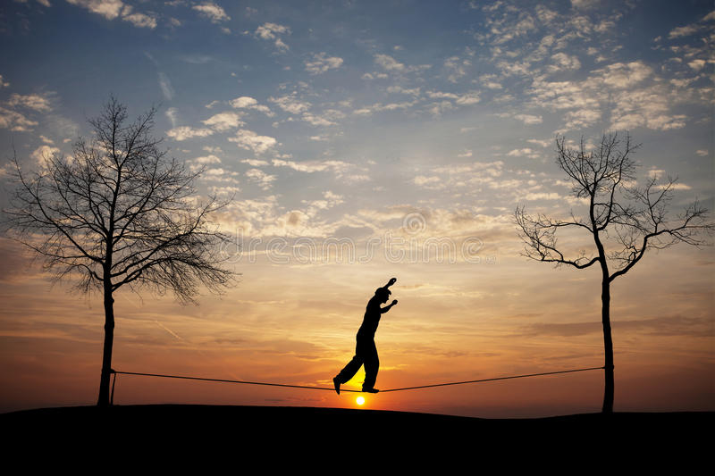 Silhouette of man on slackline. In sunset stock photography