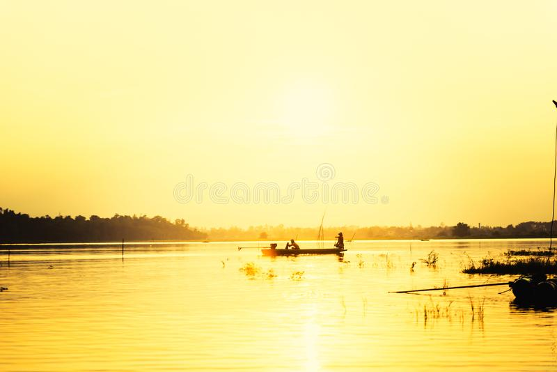 Silhouette man in small fishing boat at lake with mountain view against sunset sky royalty free stock photos