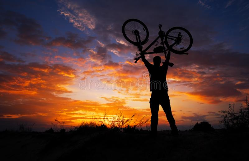 Silhouette the man stand in action lifting bicycle. Above his head on the meadow with sunset stock photography