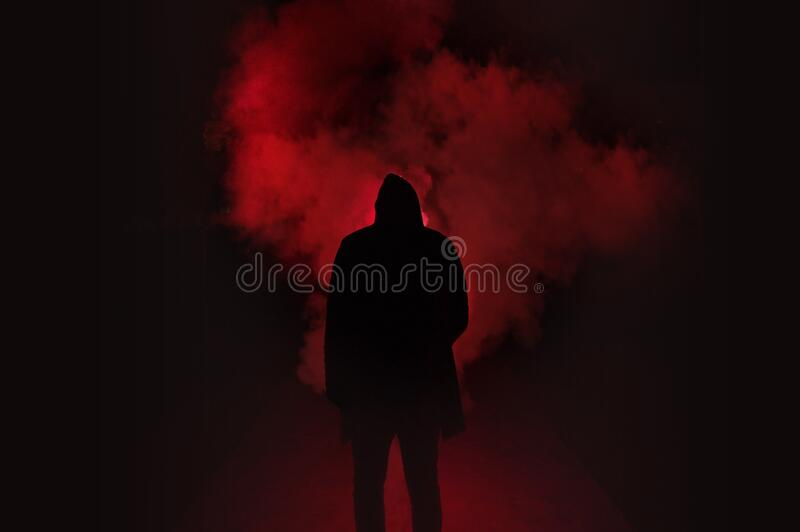 Silhouette of Man Standing Against Black And Red Background stock photography