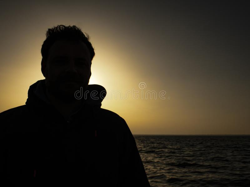Silhouette of a man standing on against the sunset near the sea.  stock photos