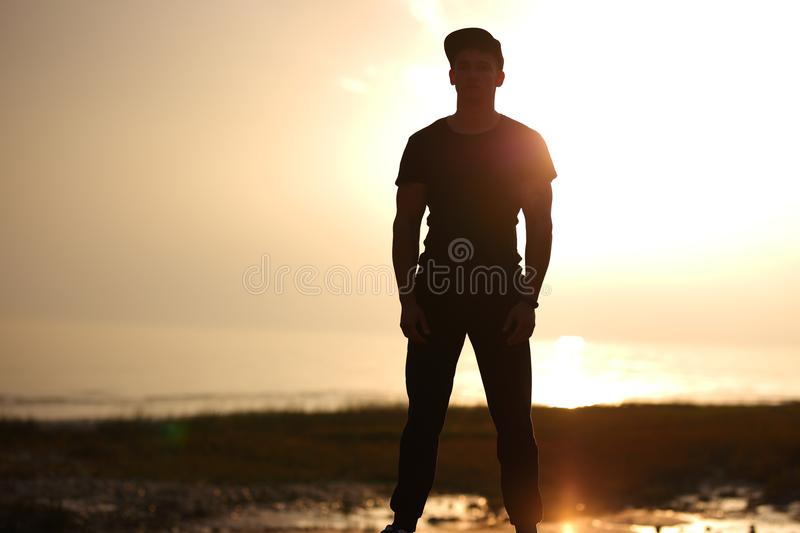 Silhouette of man standing on beach in the sunset at the sea. Silhouette of man standing on beach in the sunset at the sea royalty free stock photos