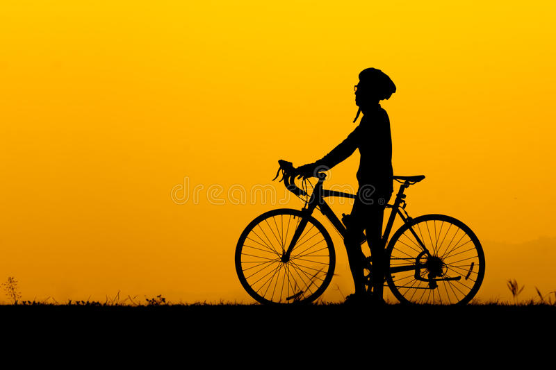 A silhouette of man standing with bicycle stock images