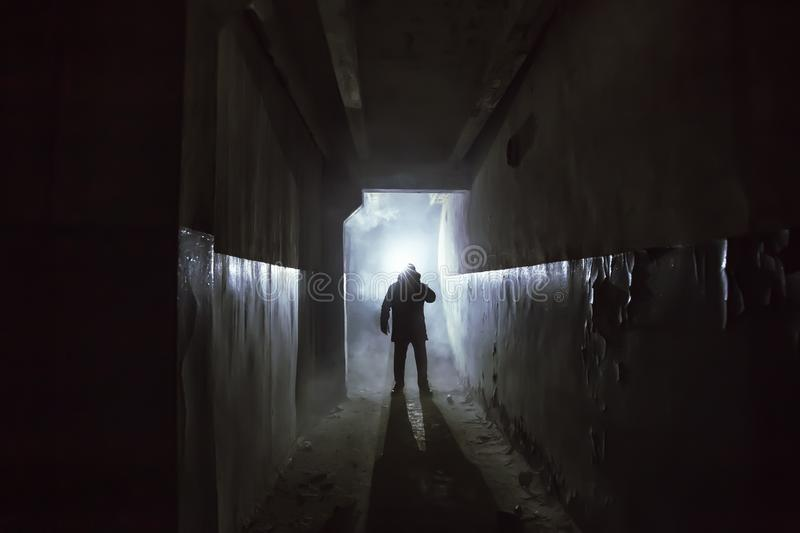 Silhouette of man in standing in dark scary corridor or tunnel with back light stock photos