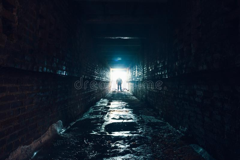 Silhouette of man standing in dark underground corridor. Light at end of tunnel concept royalty free stock images