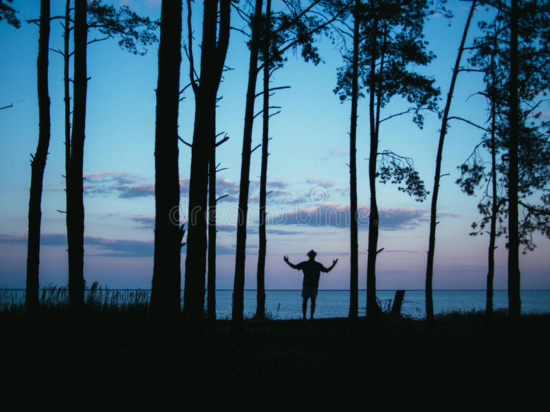 Silhouette man standing in forest rising hands with sea sunset background stock photos