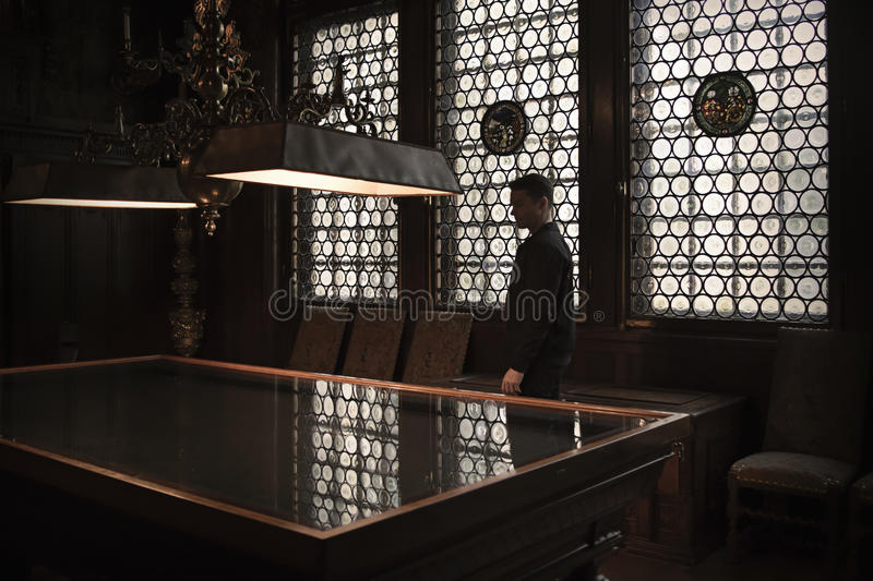 Silhouette of man standing by a grand table in an old house. Leaded windows letting in light from behind him. stock photo