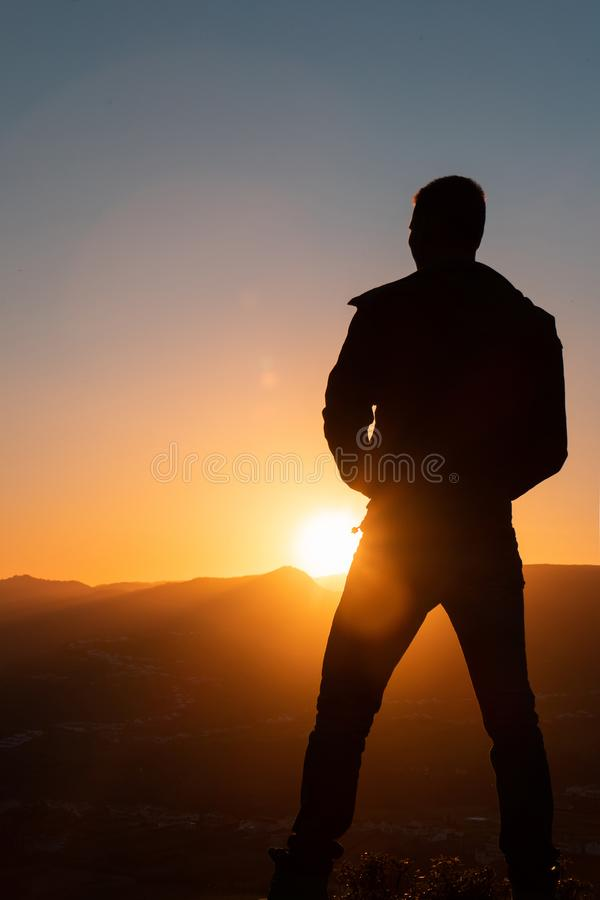 Silhouette of man standing a lone on top of mountain with orange twilight in the dark evening light from the back.  royalty free stock photography
