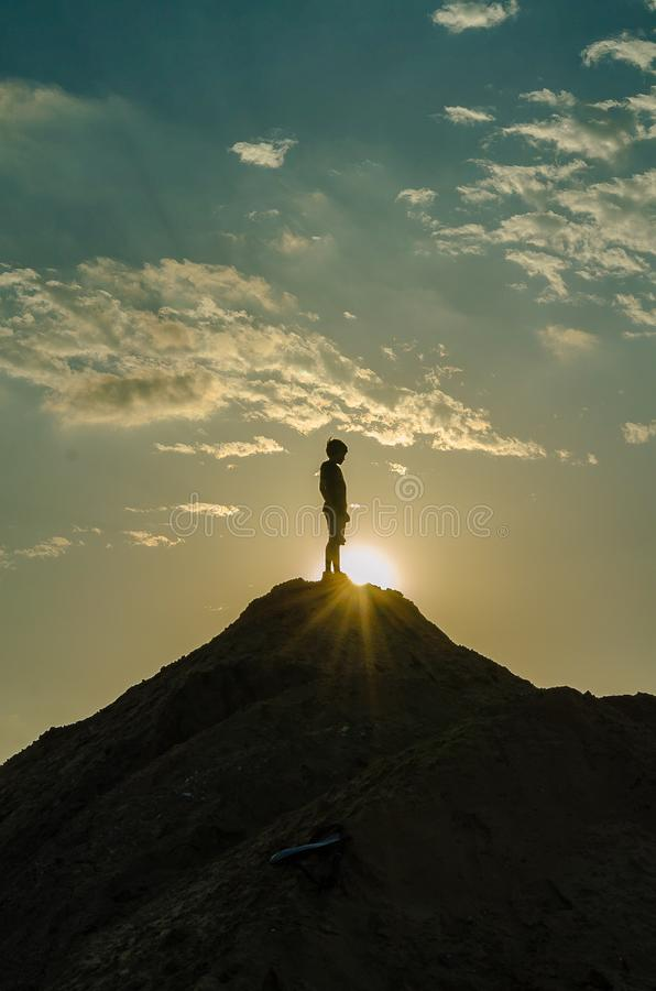 Silhouette of a Man Standing on a Mountain stock image