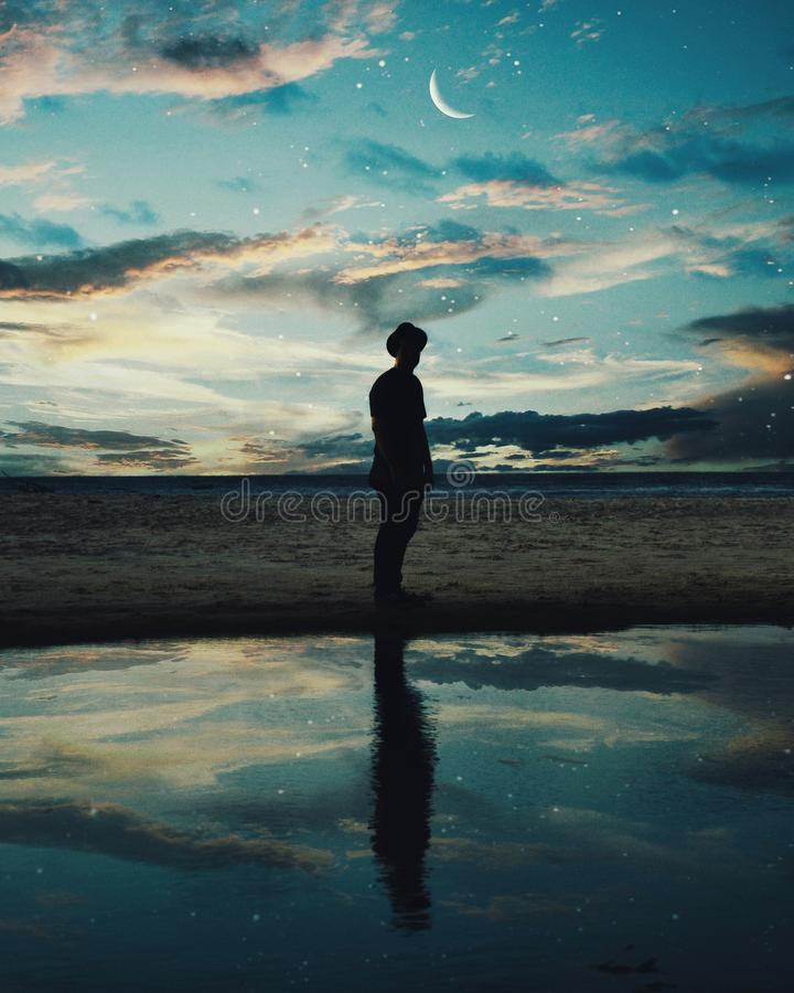 Silhouette of Man Standing Near Body of Water royalty free stock photo