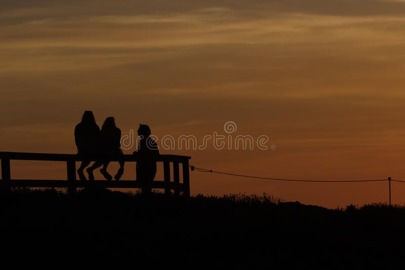 Silhouette of a man standing next to two girls sitting on a fence at sunset. Along California`s Big Sur coast stock photo