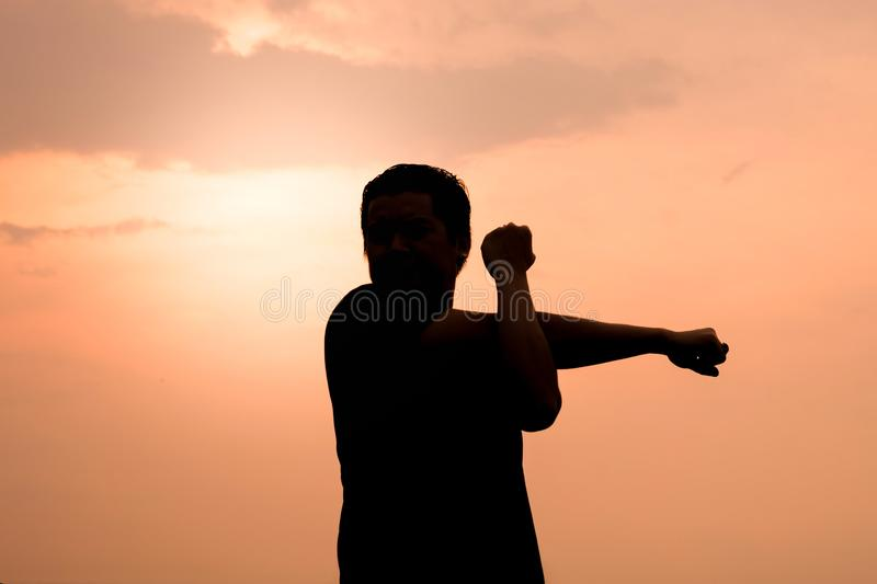 Silhouette of a man Stretch the muscles exercises royalty free stock photo