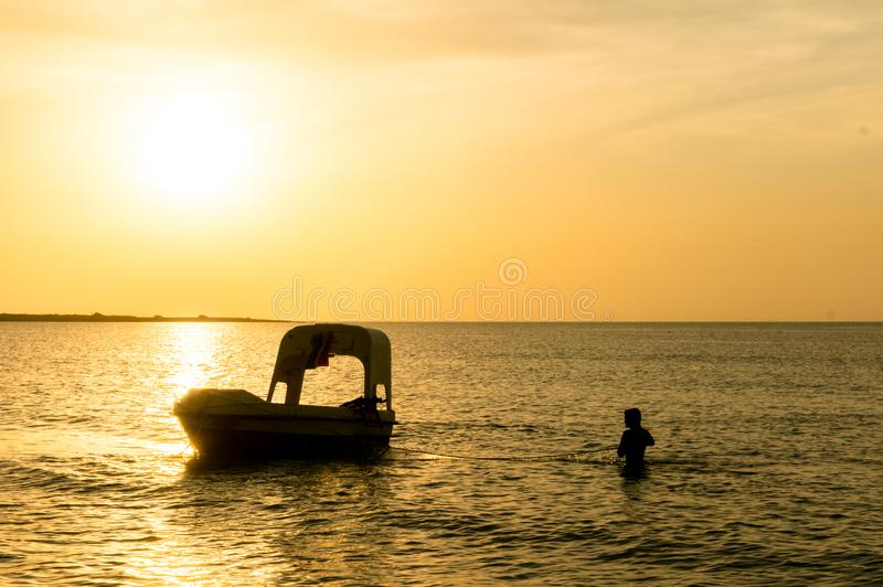 Silhouette of a man taking anchor for a boat with setting sun in the distance. Modern boats like this offer scuba diving lessons for tourists at Shivrajpur royalty free stock photos