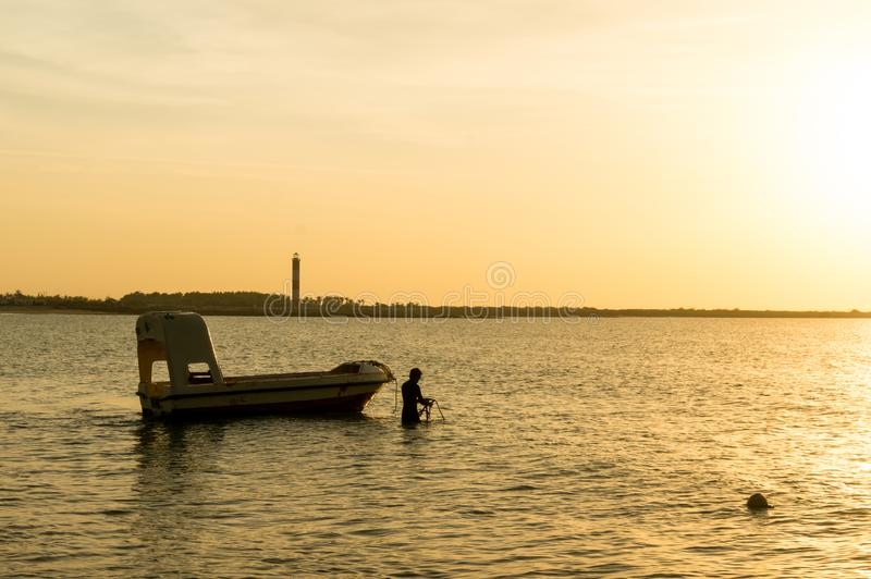 Silhouette of a man taking anchor for a boat with setting sun in the distance. Modern boats like this offer scuba diving lessons for tourists at Shivrajpur stock images