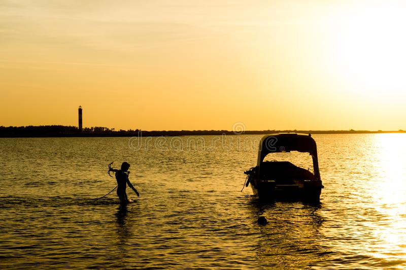 Silhouette of a man taking anchor for a boat with setting sun in the distance. Modern boats like this offer scuba diving lessons for tourists at Shivrajpur stock photo