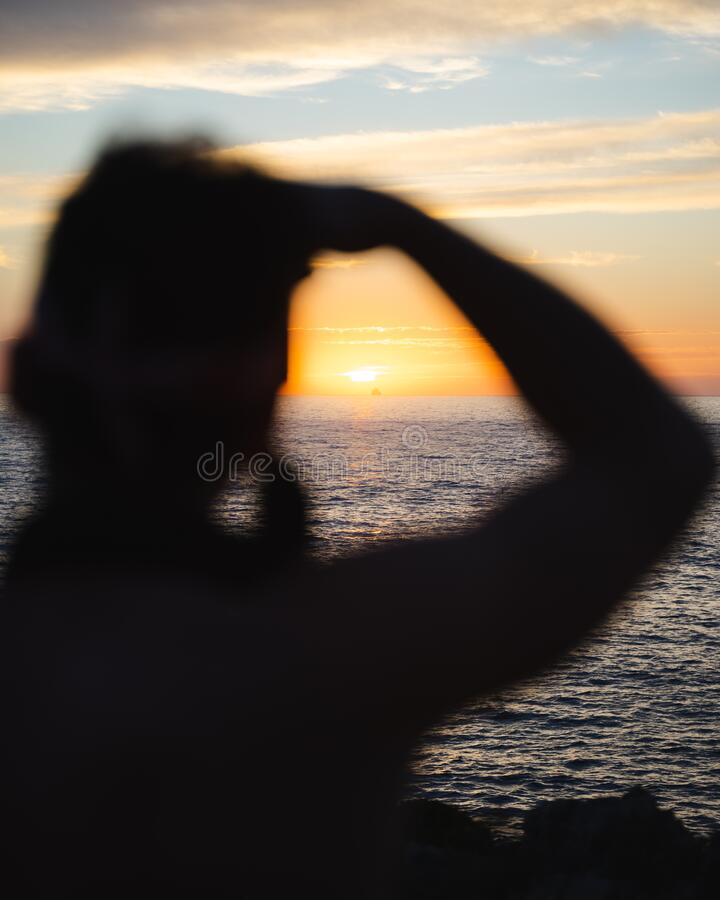 Silhouette of man taking picture of sunset stock photo