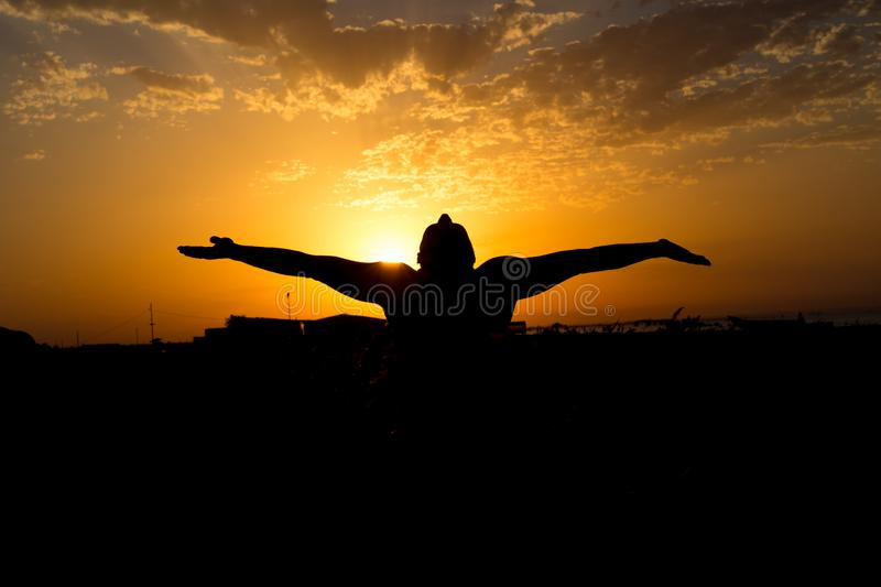 Silhouette of man with their hands in the sunset. Outdoor shot. Silhouette of man with their hands in the sunset royalty free stock photos