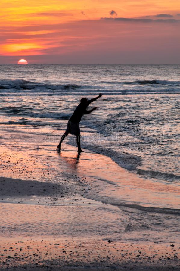 A silhouette of a man throwing a cast net for bait fish with the. Colors of sunset reflecting on the ocean and beach stock photos
