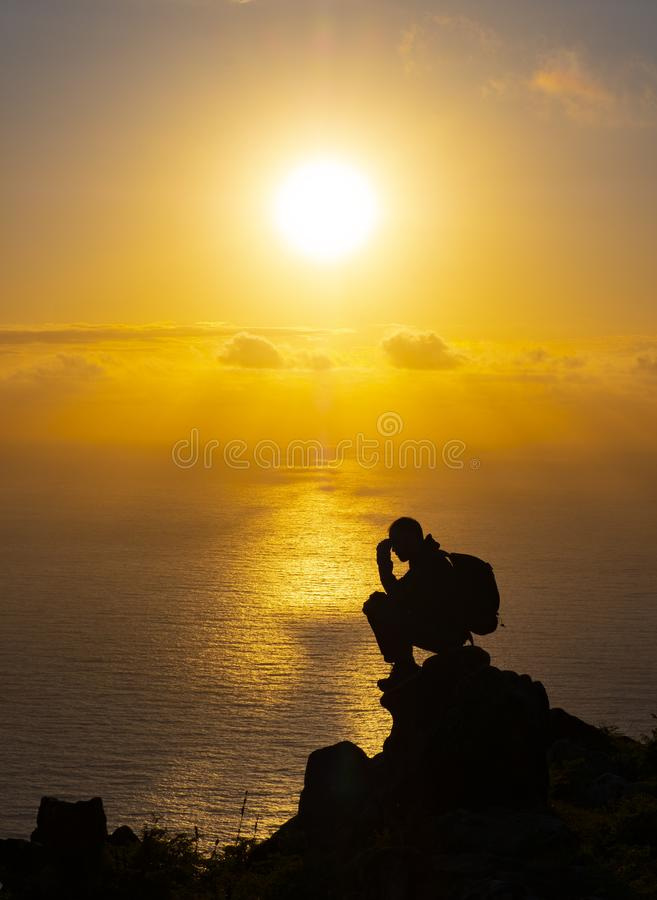 Silhouette of man on top sitting meditating at sunset with sun and sea stock images