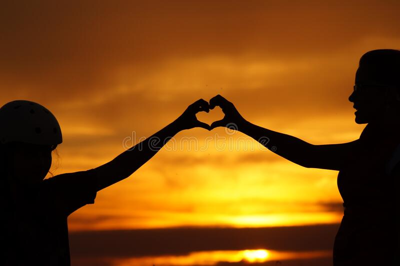Silhouette of Man Touching Woman Against Sunset Sky royalty free stock images