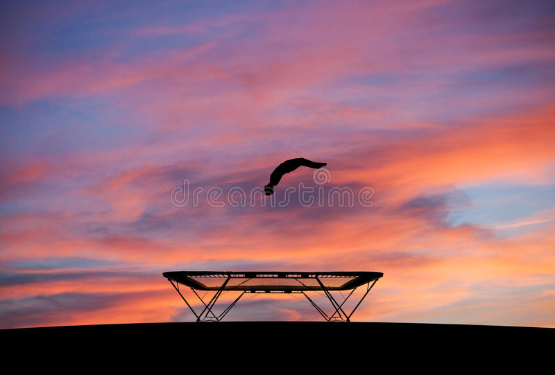 Silhouette of man on trampoline in sunset. Silhouette of man jumping on trampoline in sunset stock image