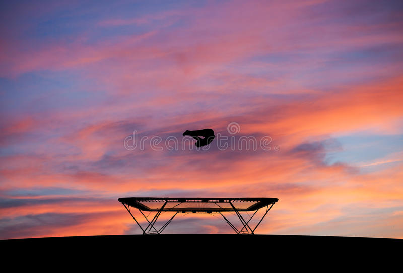 Silhouette of man on trampoline in sunset. Silhouette of man jumping on trampoline in sunset stock images