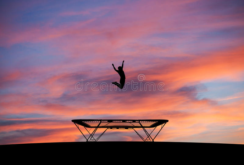 Silhouette of man on trampoline in sunset. Silhouette of man jumping on trampoline in sunset royalty free stock photos