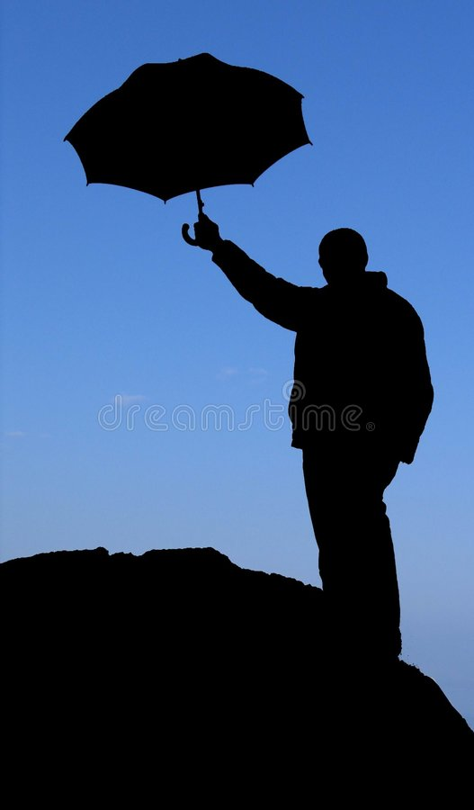 Silhouette man with umbrella on the rock royalty free stock image