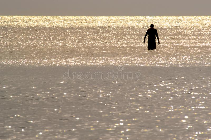 A Silhouette of a man wading in the ocean. Silhouette of a solitary man wading in shiny water in the Gulf of Mexico at sunset on Barefoot Beach, Florida stock photo