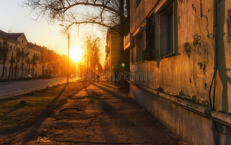 Silhouette of man walking along city street during beautiful warm sunset. stock photos