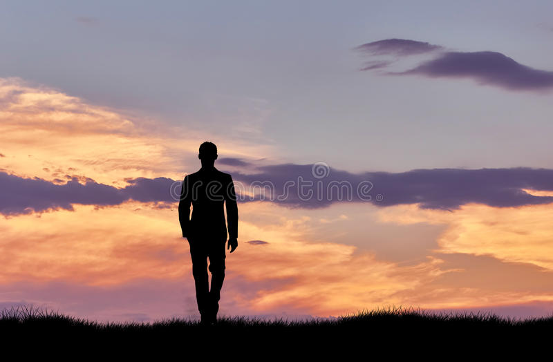 Silhouette of man walking at sunset stock images