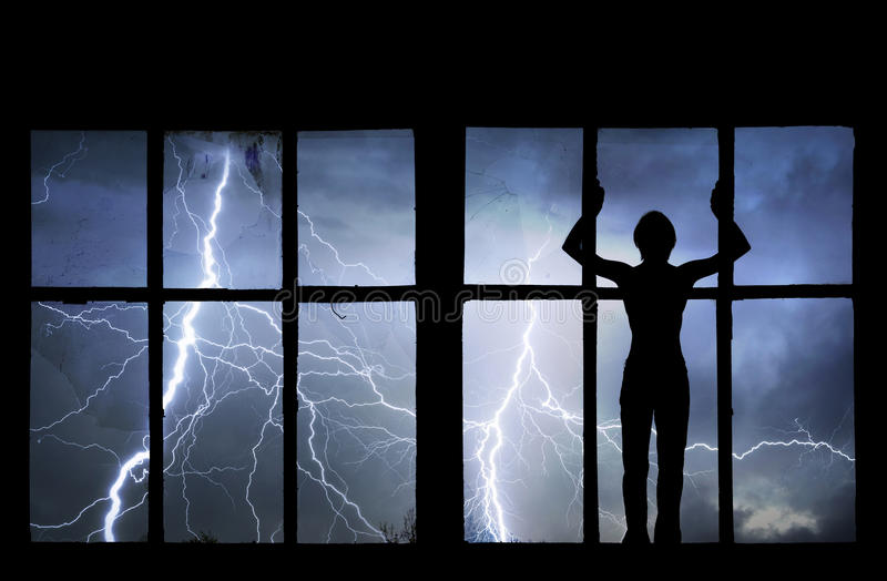 Silhouette of man watching lightning, thunder, rain and storm. Through broken window of old building royalty free stock photo