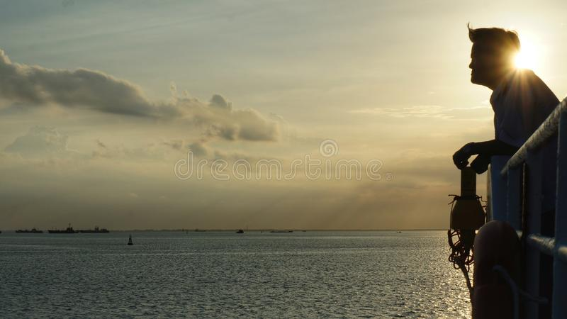 Silhouette of Man Watching the Ocean on Deck of Passenger Ship. At Sunset stock image