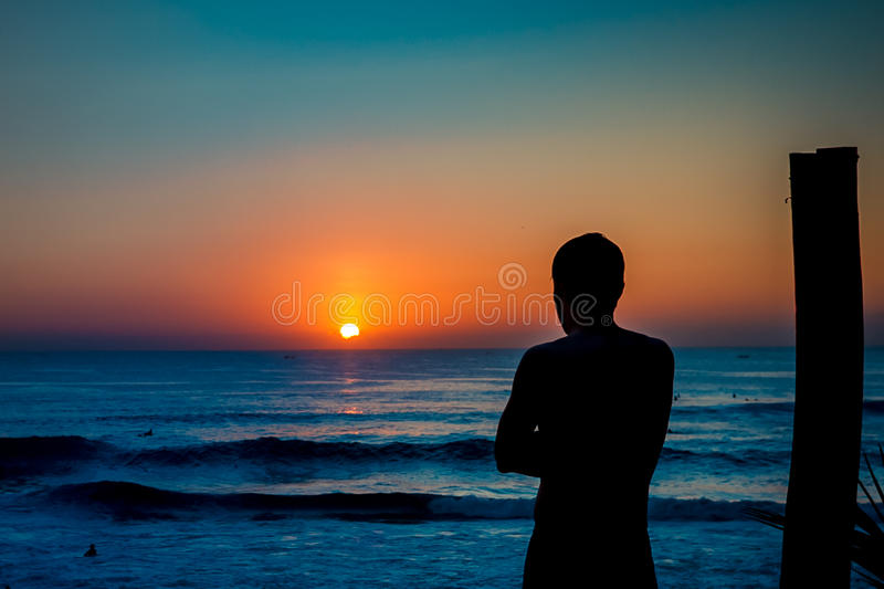 Silhouette of a man watching sunset on the beach. Silhouette of a person watching sunset scene on the beach stock image