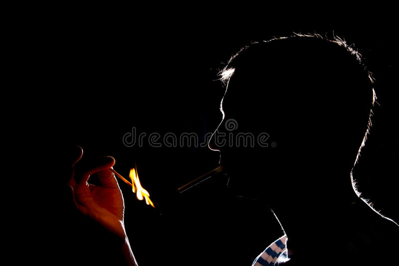 Silhouette of man who lights the cigarette in the dark royalty free stock images
