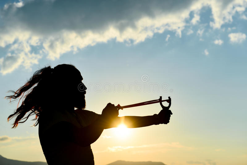 Silhouette of the man who throws slingshot stock images