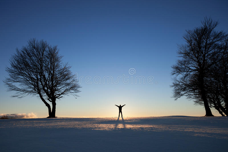 Silhouette of man in winter landscape between trees. In sunset royalty free stock image