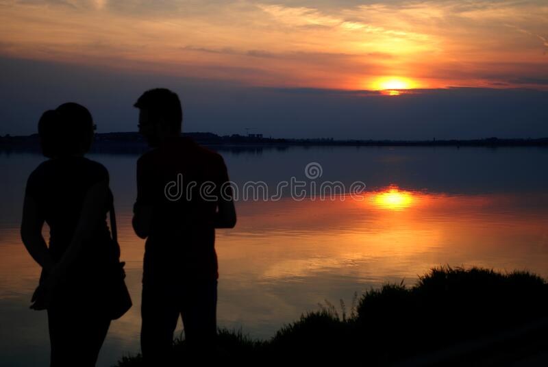 Silhouette of Man and Woman Near Water during Sun Set royalty free stock photo