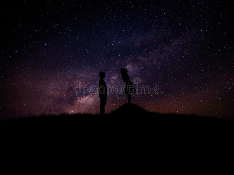 Silhouette of man and woman over grass and hill with star milky way backgrounds, romantic valentine.  royalty free stock images