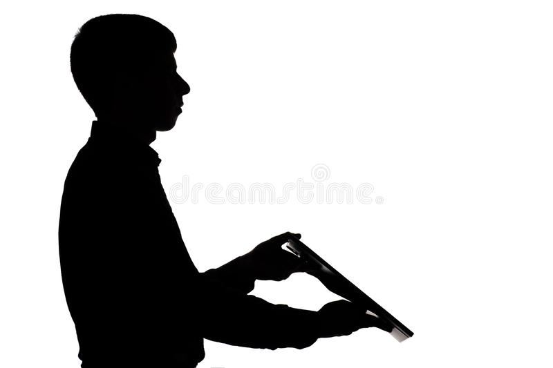 Silhouette of a man working in the company and brought the report in a folder. Silhouette of a young man working in the company and brought the report in a stock images